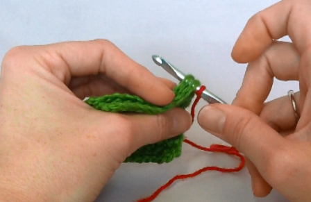 Since I'm joining edges, I insert my hook under both loops of both pieces in the first stitch at the corner.